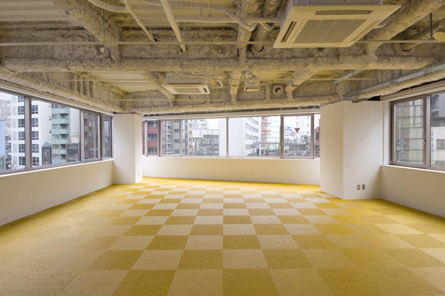 3面が窓の明るいオフィス。ビビットな色合いの床材が映える空間。